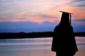 Identity and Destiny Graduation as graduate looks across a lake